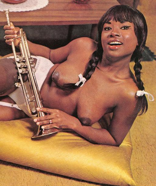black girl with pigtails and a brass instrument shows off her pretty boobs